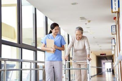 therapist walking next to a stroke survivor using a walker to practice gait training