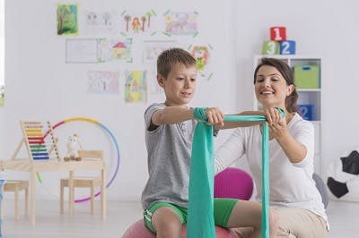 child with cerebral palsy practicing core-engaging exercises to promote better posture and balance