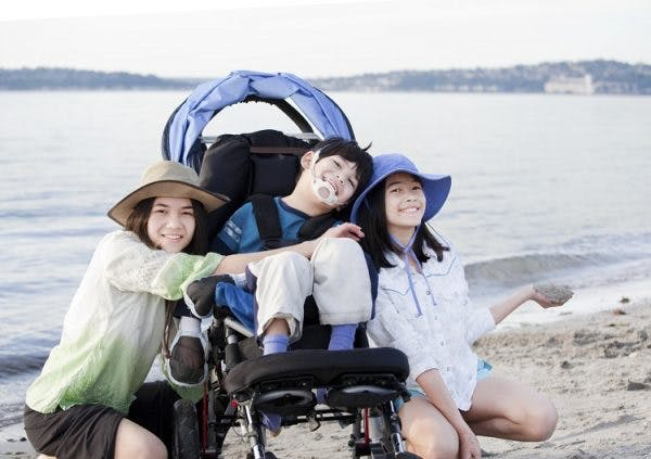 child with a type of cerebral palsy called spastic quadriplegia at the beach with family