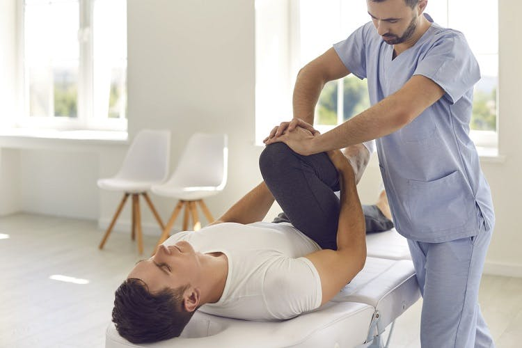 indiviual experiencing spasticity after spinal cord injury participating in physical therapy to stretch muscles