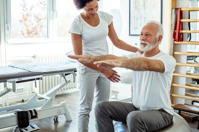 physical therapist working with stroke patient in inpatient rehabilitation facility during early stroke recovery timeline