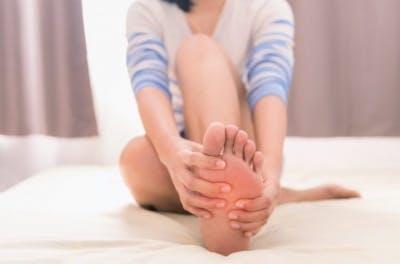 mujer sosteniendo su pie