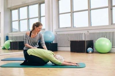 Profesora de yoga certificada ayudando a un paciente de accidente cerebrovascular a modificar la pose de yoga