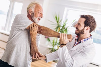 man practicing physical therapy exercises to relieve muscle stiffness after stroke
