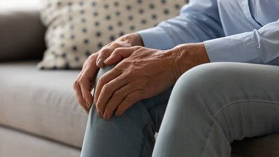 elderly woman experiencing knee pain due to stiff muscles