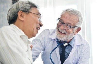 médecin et patient ayant subi un AVC s'amusant à discuter du traitement de l'AVC