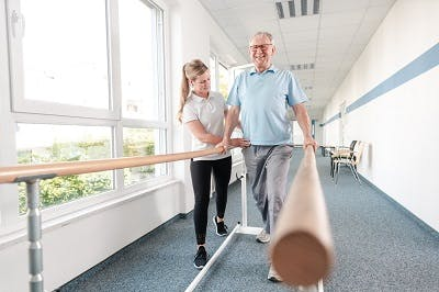man with paraplegia after thoracic spianl cord injury practicing walking