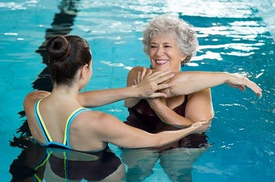 woman with spinal cord injury practicing exercises in a pool