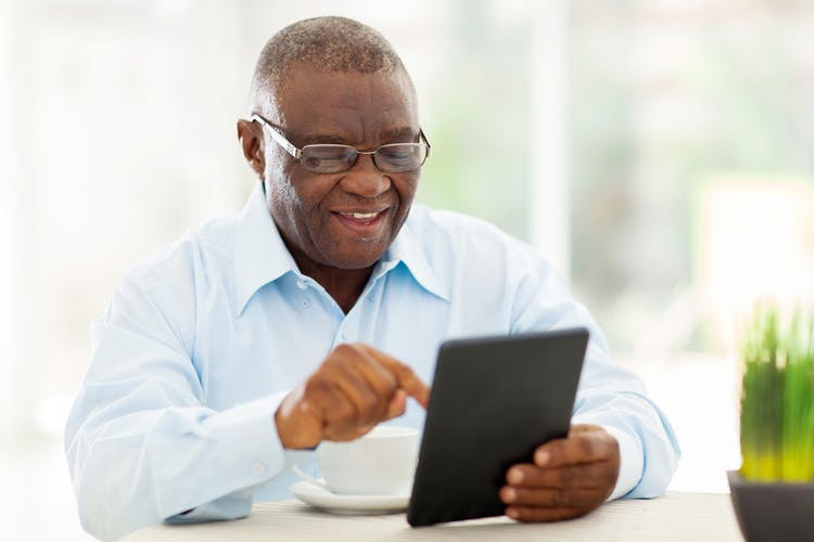 senior man doing cognitive rehabilitation exercises on tablet to improve memory after stroke