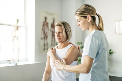 physical therapist helping stroke patient move affected arm through range of motion