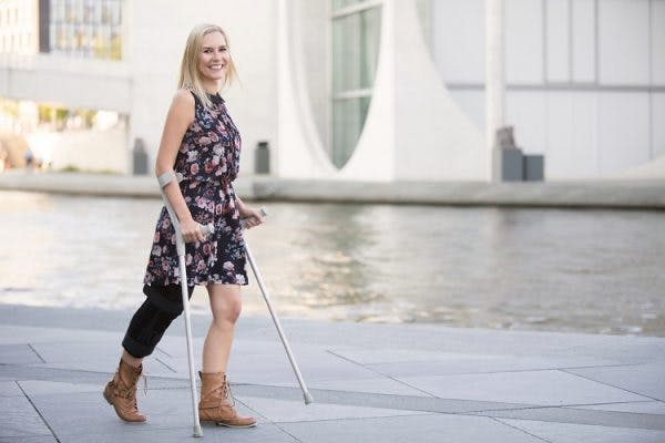 woman with cerebral palsy in the legs walking with crutches