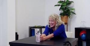 thérapeute poussant une bouteille d'eau sur une table avec des bras