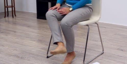thérapeute donnant un coup de pied à la jambe vers l'intérieur pour l'exercice des adducteurs de la hanche