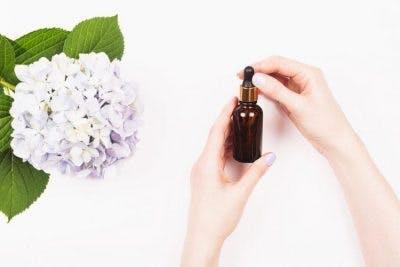Mujer sosteniendo una botella ámbar de regalo de aceite de magnesio para pacientes con accidente cerebrovascular