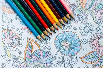 coloring book with colored sheets and pencils