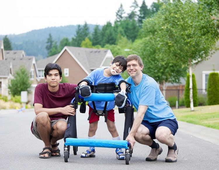 boy with abnormal walking pattern called crouch gait due to cerebral palsy using a walker