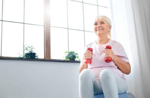 patient d'AVC faisant de l'exercice à la maison avec un ballon médicinal et des haltères
