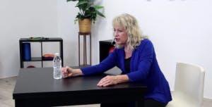 thérapeute poinçonnant une bouteille d'eau pour l'ergothérapie