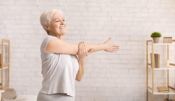 une patient victime d'un AVC fait des exercices pour les bras à la maison