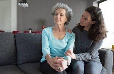 fille sur le canapé essayant de parler à une mère en colère, se demandant comment aider quelqu'un qui a eu un accident vasculaire cérébral