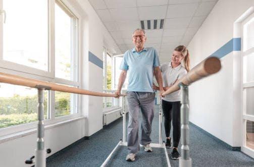 Patient d'AVC de sexe masculin utilisant des barres d'appui pour marcher pendant la séance de rééducation des patients hospitalisés