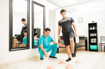 Physical therapist motivating male patient to walk between cones in hospital to promote neuroplasticity