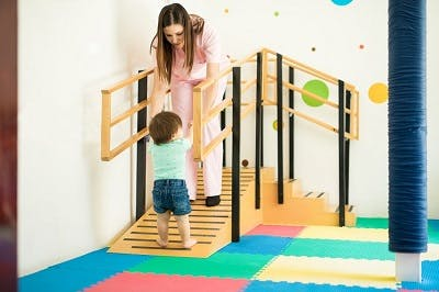 toddler with spastic diplegia practicing walking at pediatric physical therapy
