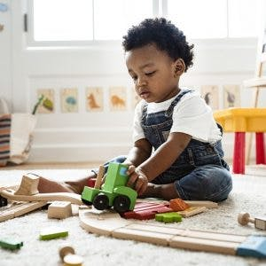 Cute little boy with cerebral palsy playing with a railroad train toy as part of play therapy