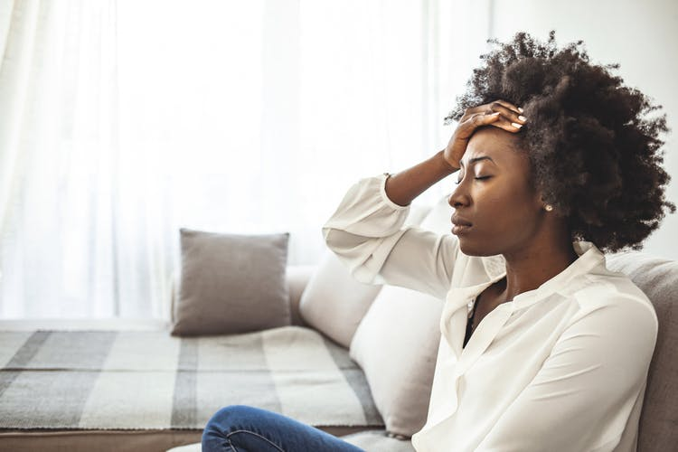 woman looking stressed out with hand on forehead