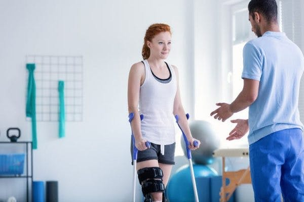 young stroke survivor with crutches participating in physiotherapy to recover her gait and ability to walk
