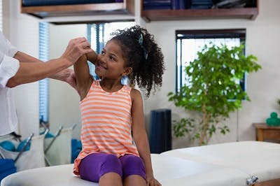 physical therapist helping young girl with rare type of cerebral palsy stretch