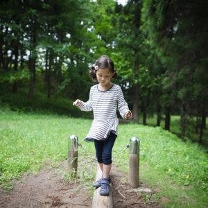 young girl with ataxic cerebral palsy practicing balance exercises outside