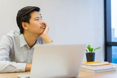 man looking out the window because he cannot focus due to brain injury