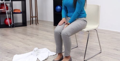 therapist seated in chair in starting position for leg exercise for walking rehabilitation