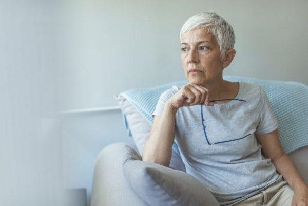 ältere Frau, die aus dem Fenster schaut, in Gedanken versunken, weil sie nach einem Schlaganfall Angst hat