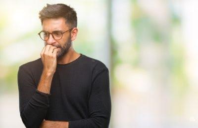Mann mit Brille, der Nägel beißt und nervös aussieht, weil er nach einem Schlaganfall Angst hat