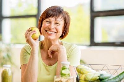 Frau, die einen Apfel hält und lächelt, weil eine Ernährungsumstellung ihr geholfen hat, mit der Angst nach einem Schlaganfall fertig zu werden