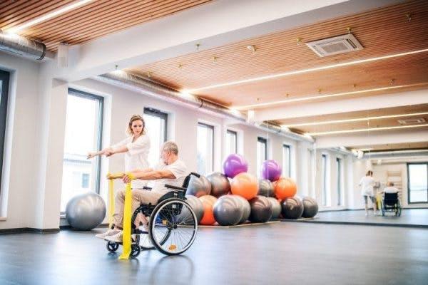 Physiotherapeut, der mit Hemiplegiepatienten in einer geräumigen Physiotherapieklinik arbeitet