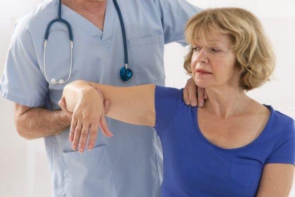 Schlaganfallpatient mit steifen Muskeln nach Schlaganfall, der mit Physiotherapeut arbeitet