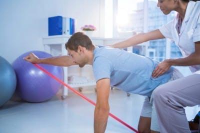 Therapeut, der Hemiplegiepatienten beim Training in der Physiotherapieklinik hilft