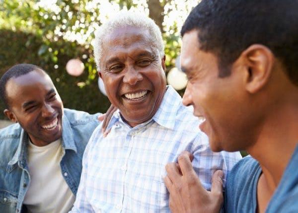 Zwei erwachsene Söhne lachen mit einem älteren Vater, der einen Schlaganfall hatte