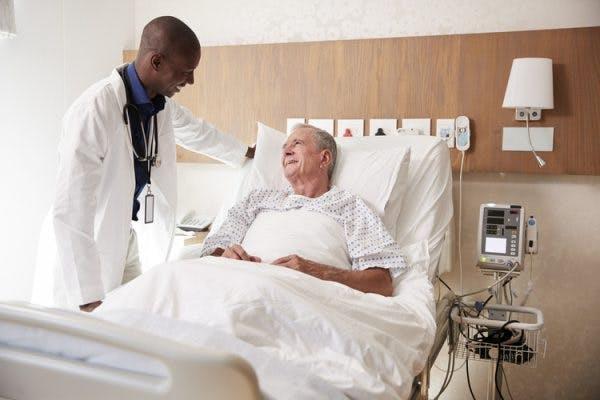friendly doctor talking to bedridden stroke patient