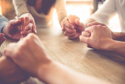 Nahaufnahme einer Gruppe von Menschen, die im Nachmittagslicht Händchen um den Tisch halten?