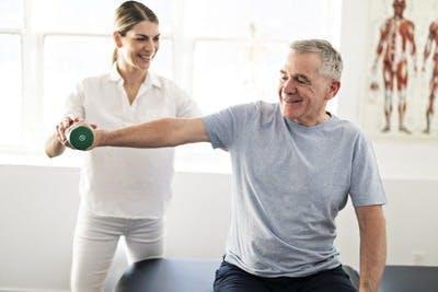 Fisioterapeuta mostrando ejercicios a sobreviviente de accidente cerebrovascular talámico