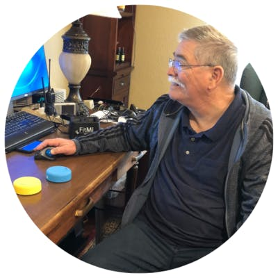 stroke survivor sitting at home office while using FitMi for therapy