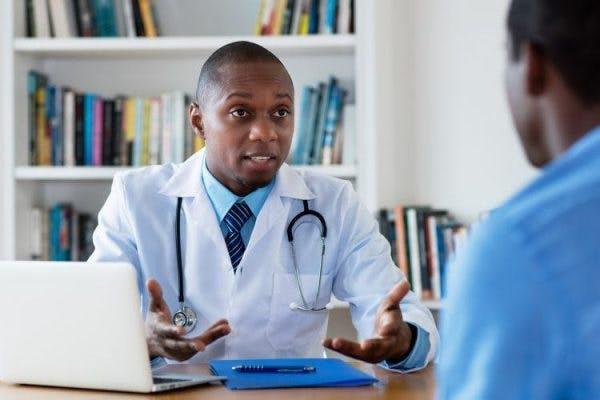 Doctor sentado en un escritorio hablando con paciente de accidente cerebrovascular del lóbulo parietal acerca de la rehabilitación