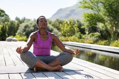 stroke survivor sitting on yoga mat meditating outside