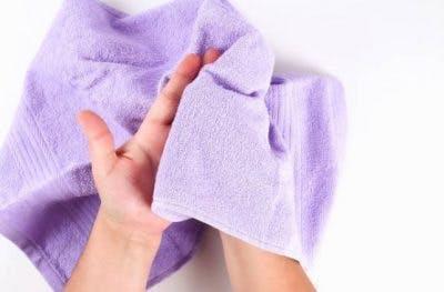 personne sentant une serviette douce pour la rééducation sensorielle
