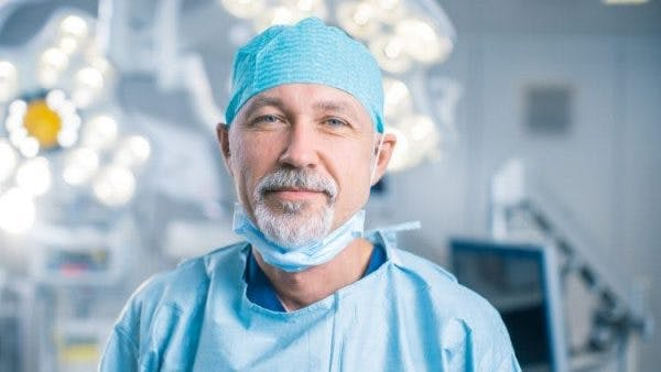 surgeon in operating room about to perform spinal cord surgery