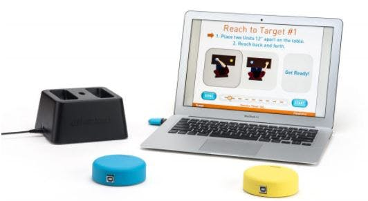 FitMi home therapy device with two interactive pucks on table with laptop